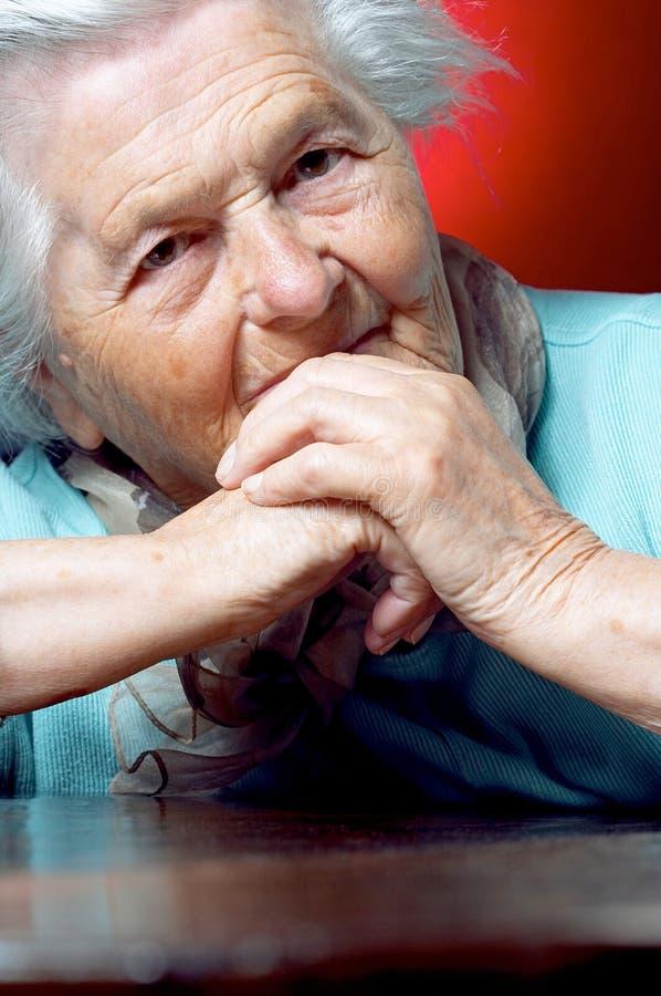 Femme aîné s'asseyant au ta image stock