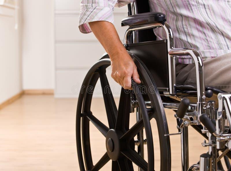 Femme aîné s'asseyant dans le fauteuil roulant photo stock