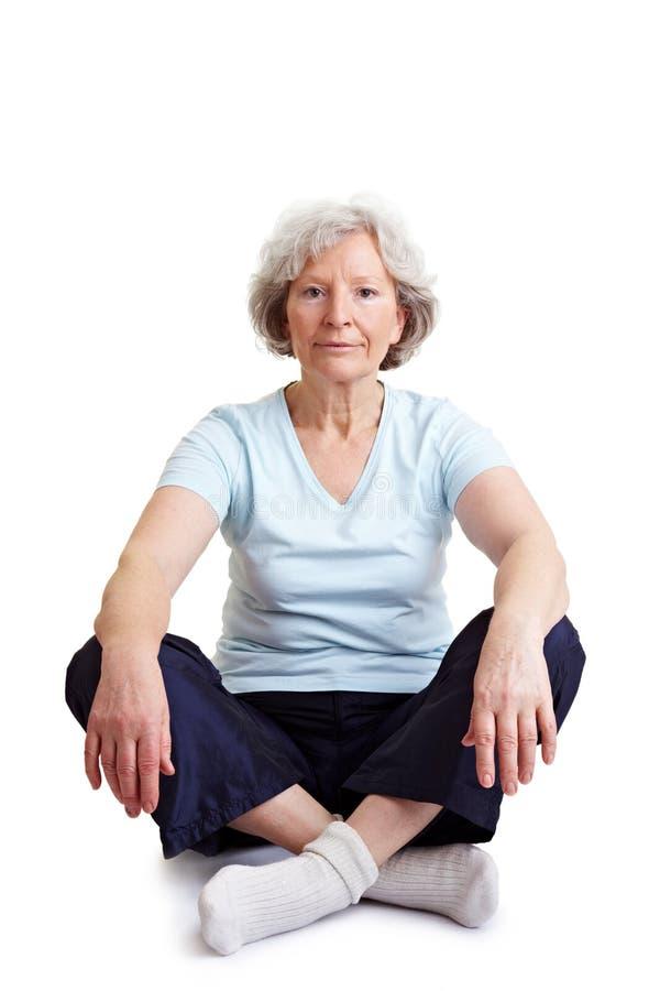 Femme aîné s'asseyant dans le siège de tailleur photo libre de droits