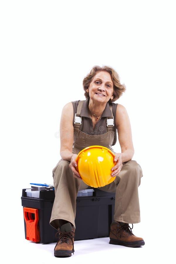 Femme aîné s'asseyant dans une boîte à outils images stock