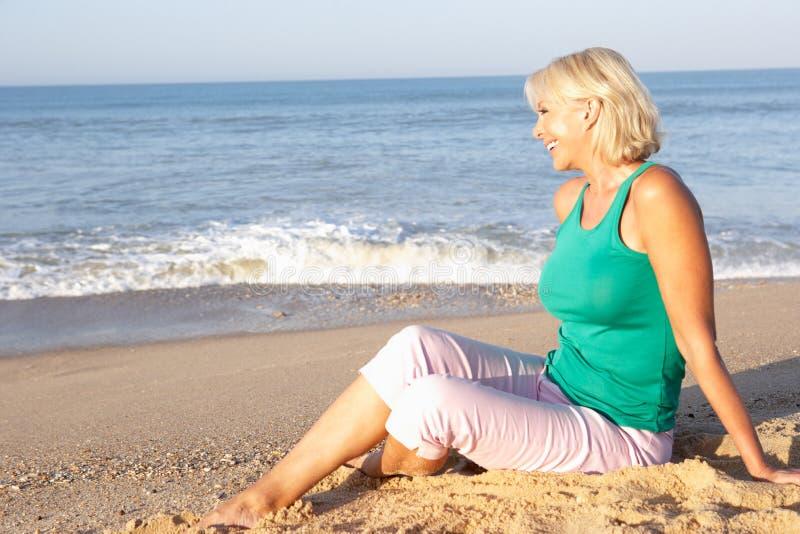 Femme aîné s'asseyant sur la détente de plage photo stock