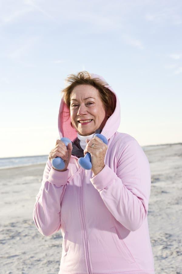 Femme aîné s'exerçant avec des poids de main sur la plage image libre de droits