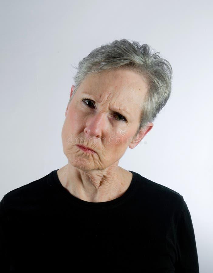 Femme aîné semblant fâché, méprisant photos stock