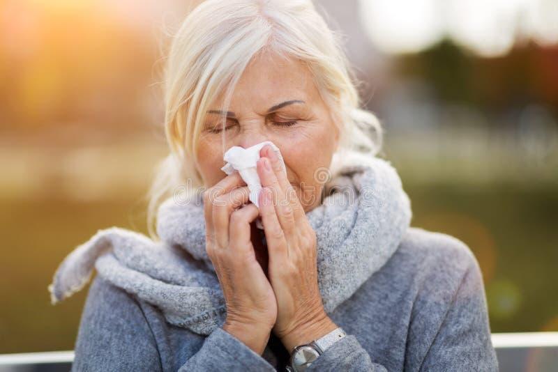 Femme aîné soufflant son nez images stock