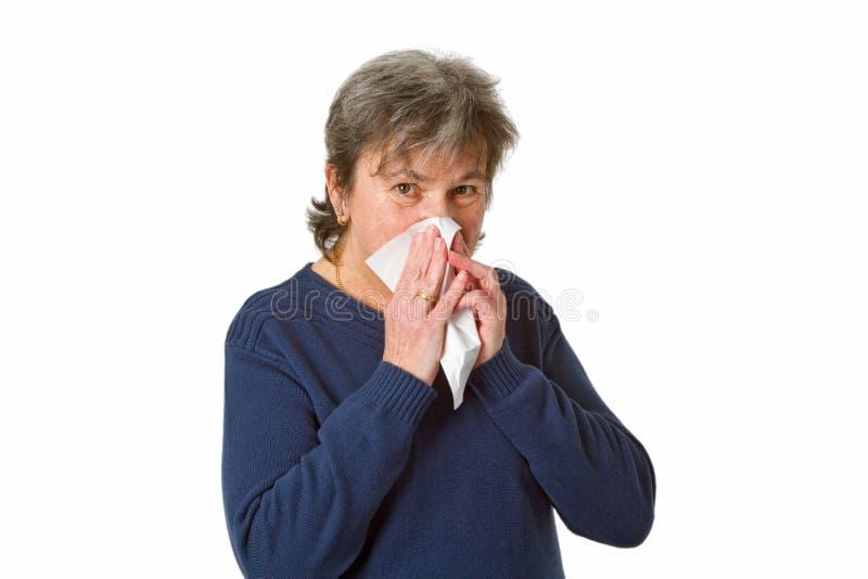 Femme aîné soufflant son nez images libres de droits