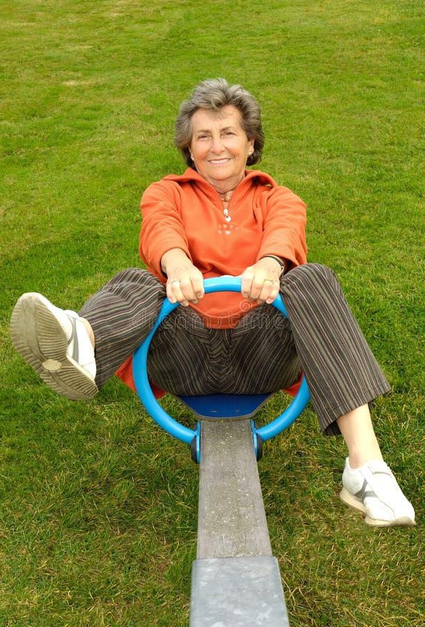 Femme aîné sur la balançoir photo libre de droits