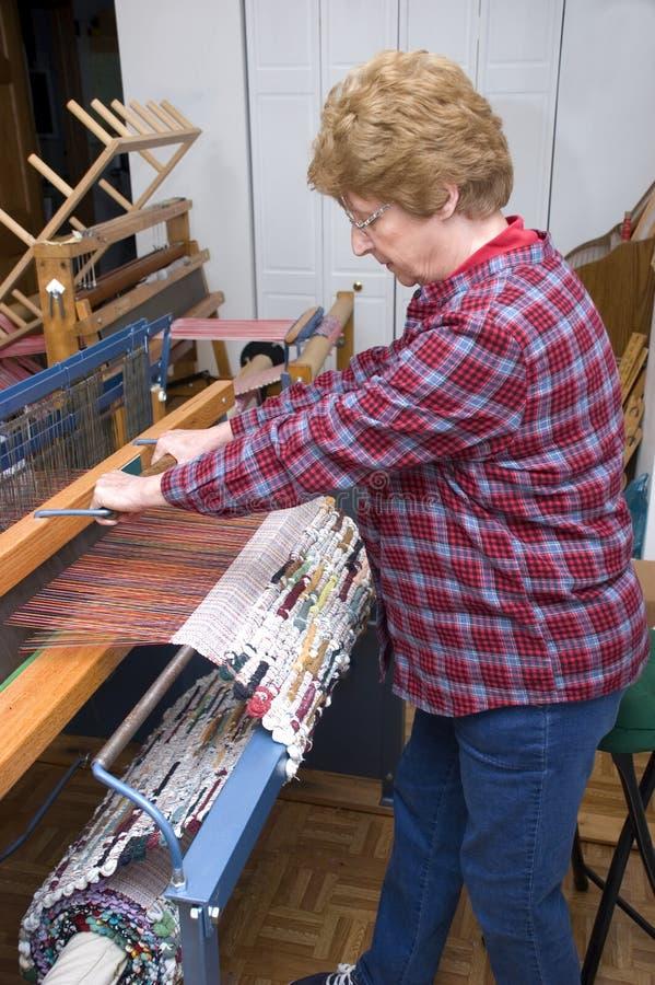 Femme aîné tissant sur le manche, artiste de textile images libres de droits