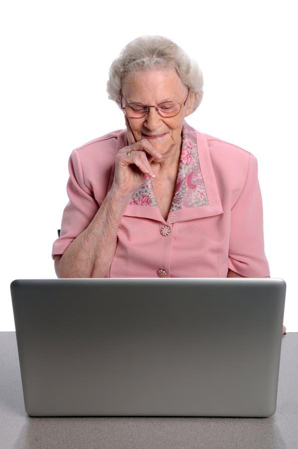 Femme aînée à l'aide de l'ordinateur photo stock