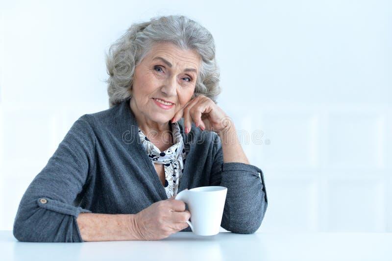 Femme aînée avec la cuvette de café photos stock