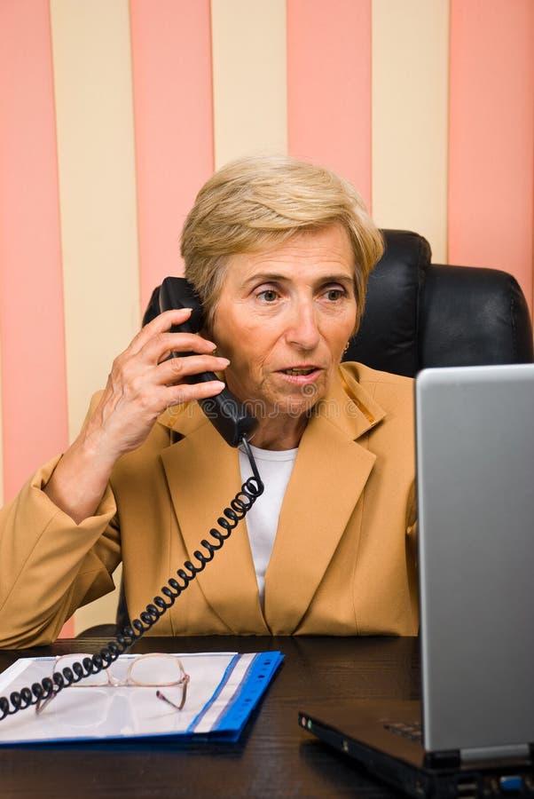 Femme aînée d'affaires travaillant dans le bureau photos stock