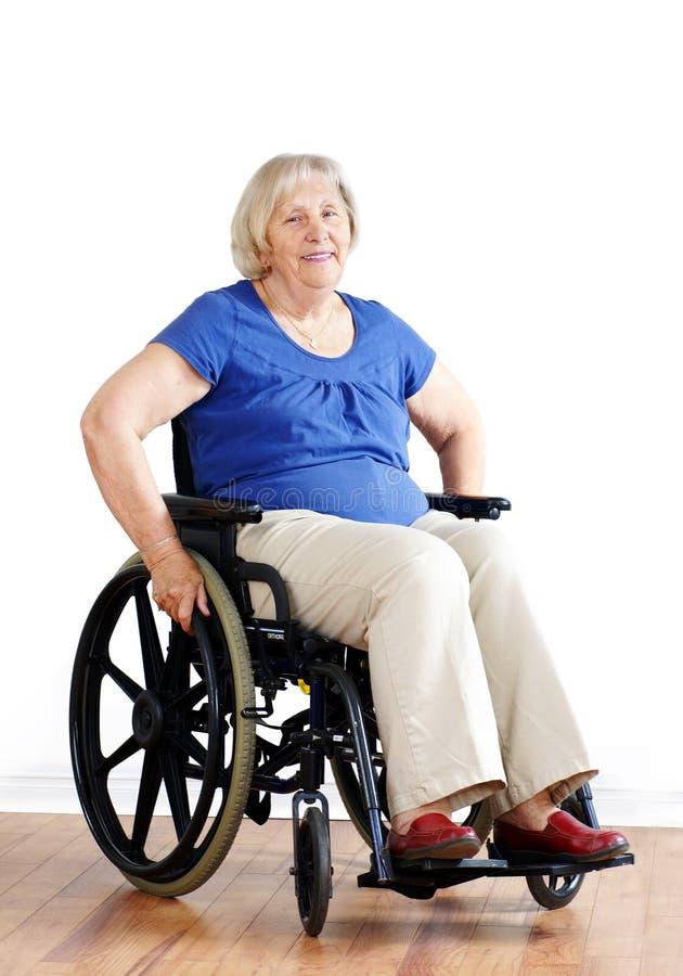 Femme aînée dans le fauteuil roulant au-dessus du blanc photos stock