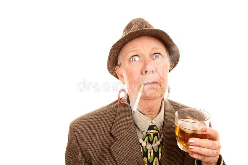 Femme aînée dans le vêtement mâle avec la cigarette et photos libres de droits