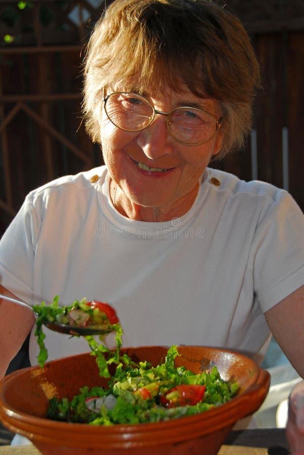 Femme aînée de consommation heureuse image stock