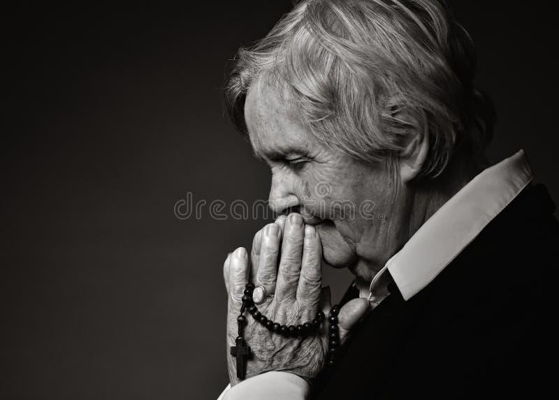 Femme aînée de prière image libre de droits