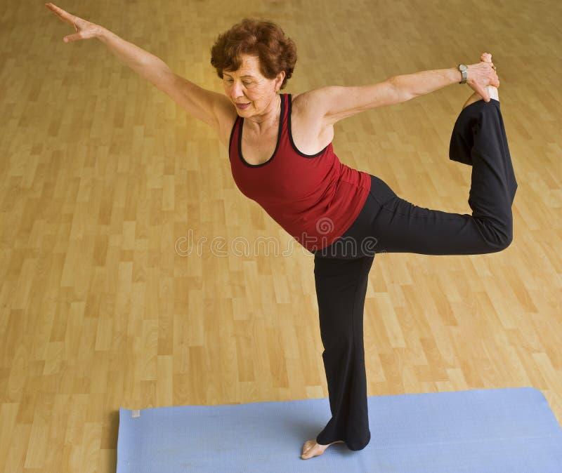 Femme aînée exerçant le yoga photographie stock libre de droits