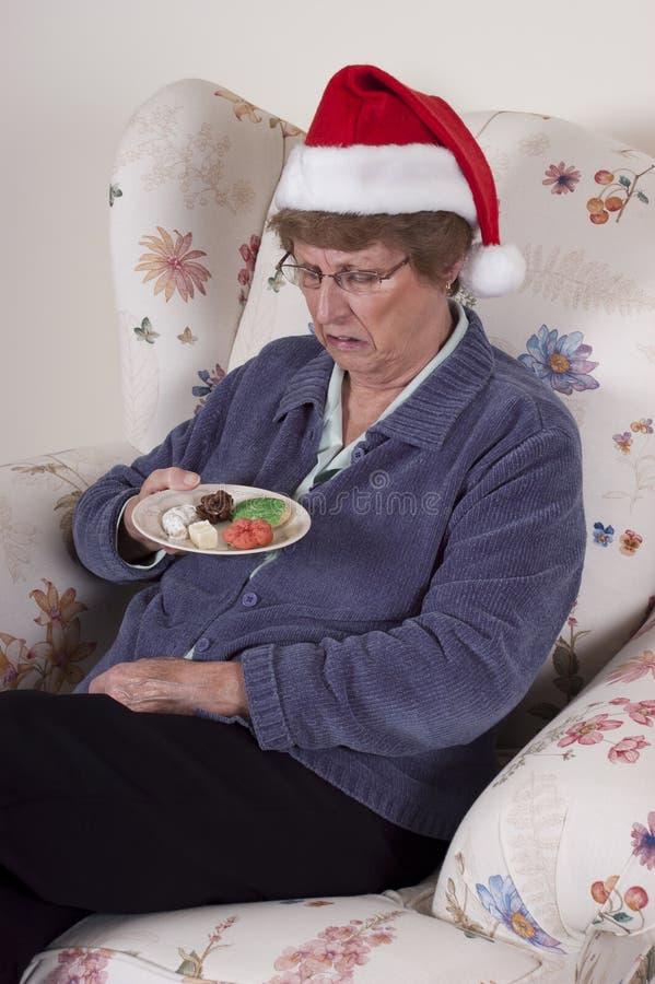 Femme aînée mûre mangeant des biscuits de vacances, casse-croûte photographie stock
