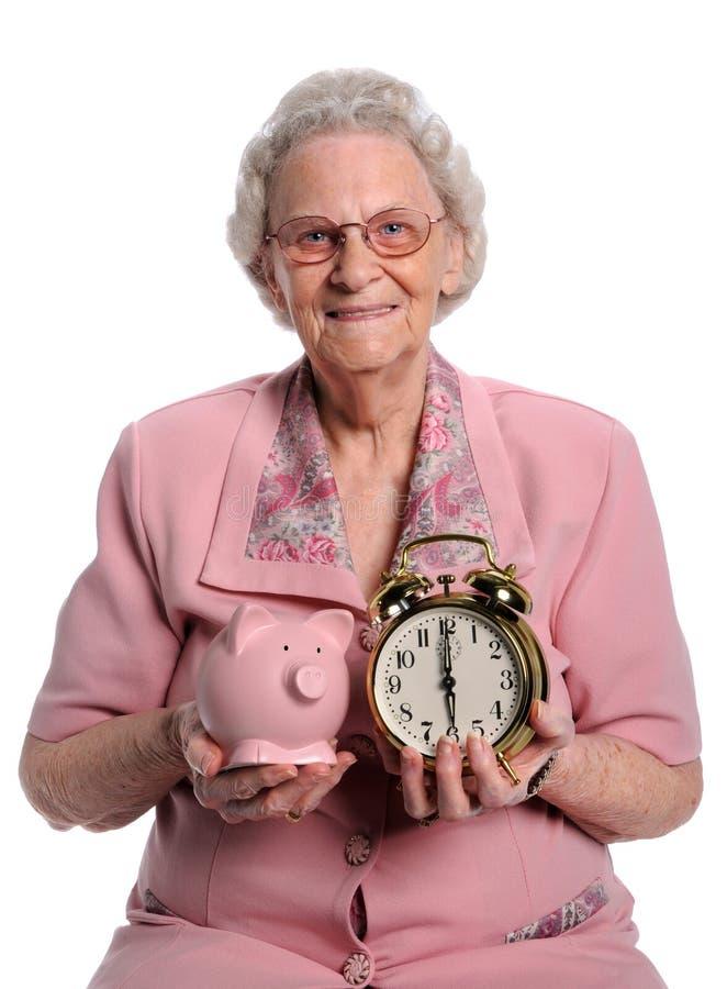 Femme aînée retenant la tirelire et l'horloge image libre de droits