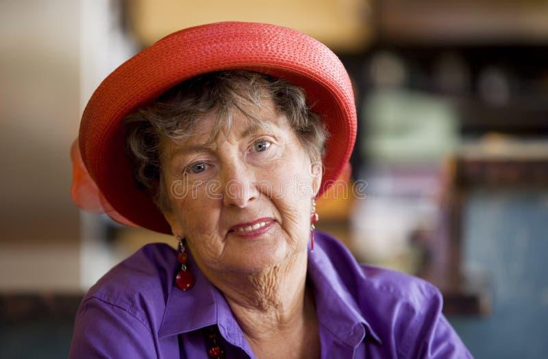 Femme aînée s'usant Red Hat photos stock