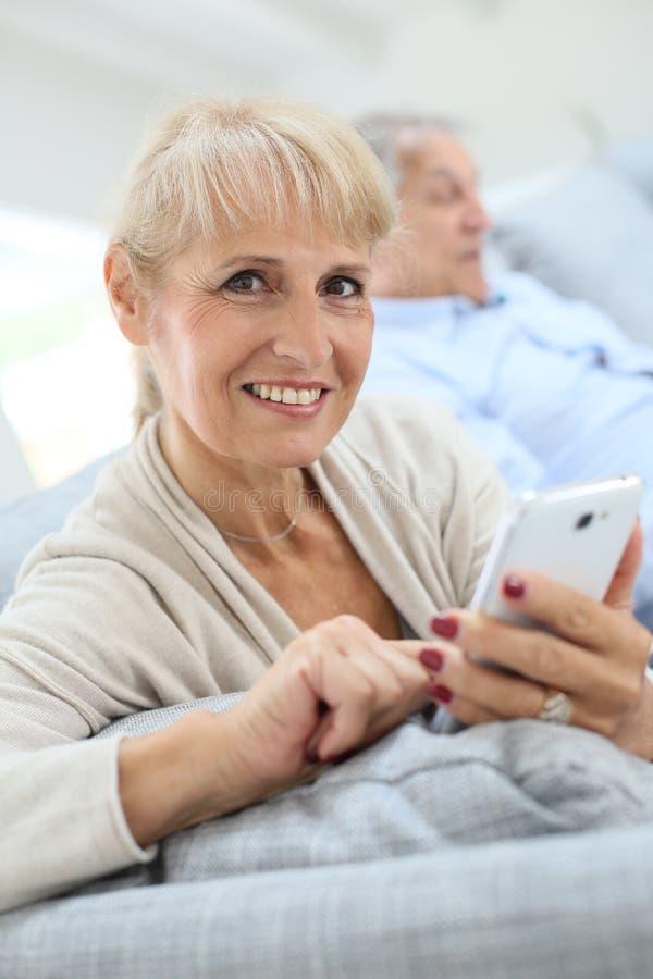 Femme aînée utilisant le smartphone images libres de droits