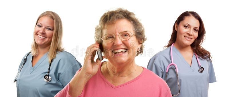 Femme aînée utilisant le téléphone portable et les médecins féminins photographie stock libre de droits