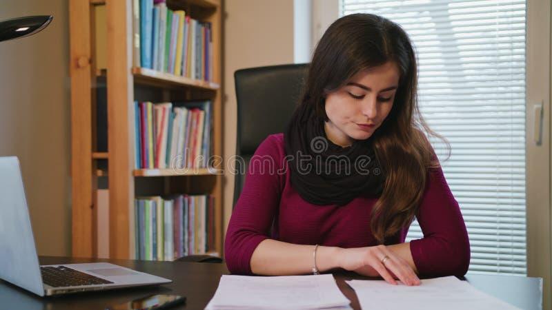 Femme accablée avec des documents et ordinateur portable dans la maison images stock