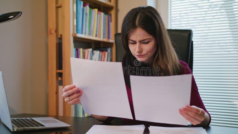 Femme accablée avec des documents et ordinateur portable dans la maison photo libre de droits