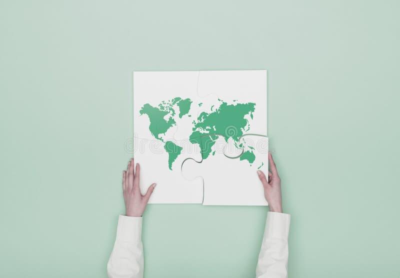 Femme accomplissant un puzzle avec une carte du monde image libre de droits