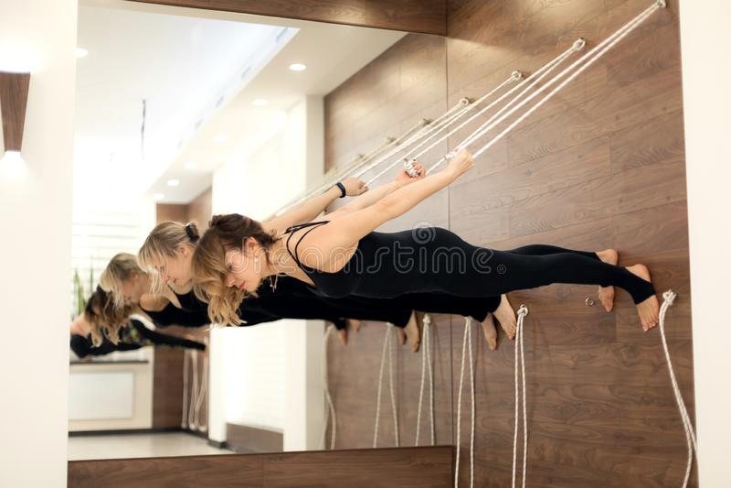 Femme accrochant sur le parall?le de corde ? linge au visage moulu en bas du yoga de pratique sur des vergetures dans le gymnase  image libre de droits