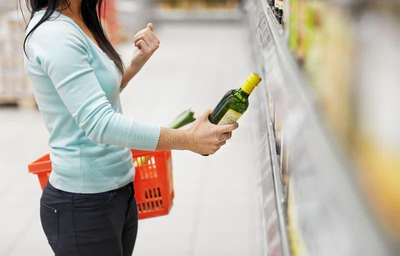 Femme achetant l'huile d'olive au supermarché ou à l'épicerie image libre de droits
