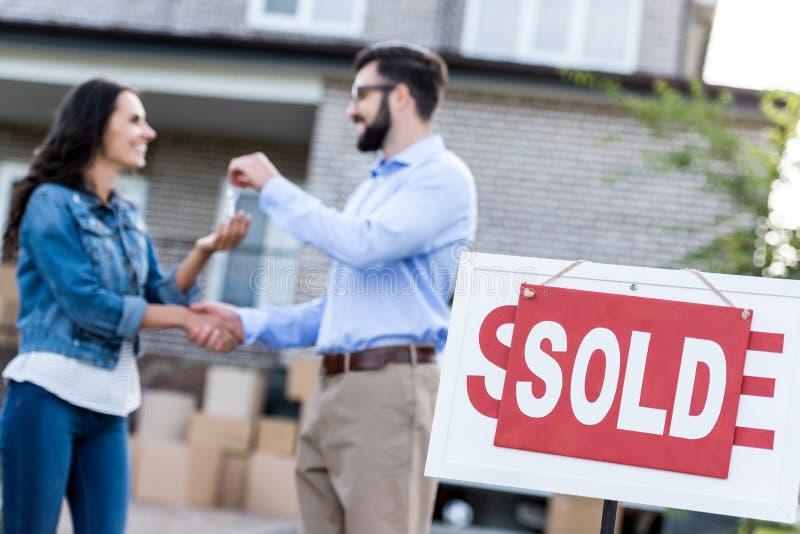 femme achetant la nouvelle maison avec l'enseigne vendue illustration de vecteur