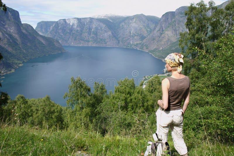Femme actif au dessus des montagnes au-dessus du lac photographie stock libre de droits
