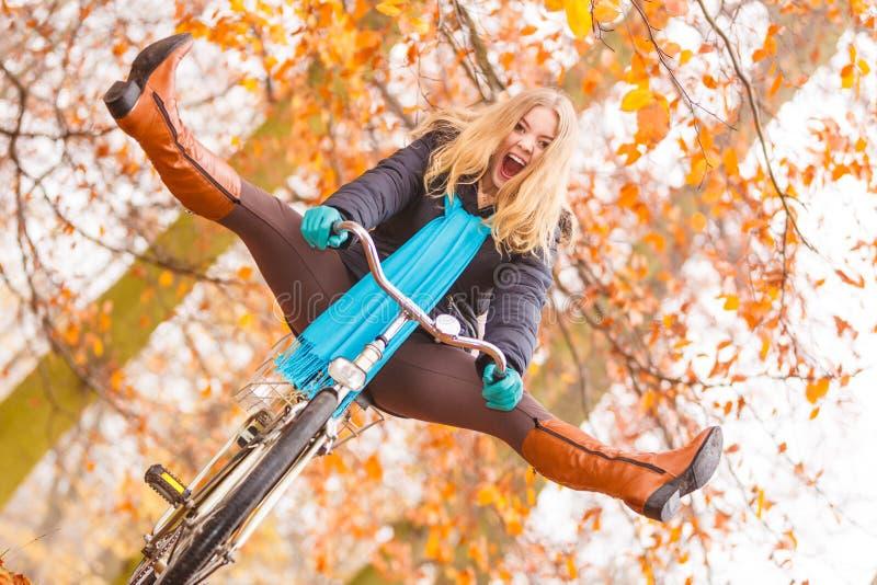 Femme active ayant le vélo d'équitation d'amusement dans le parc d'automne image libre de droits