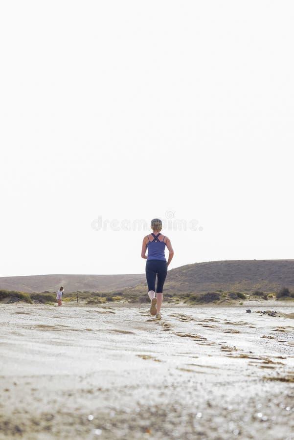 Femme active dans le désert fonctionnant dans la distance photos libres de droits