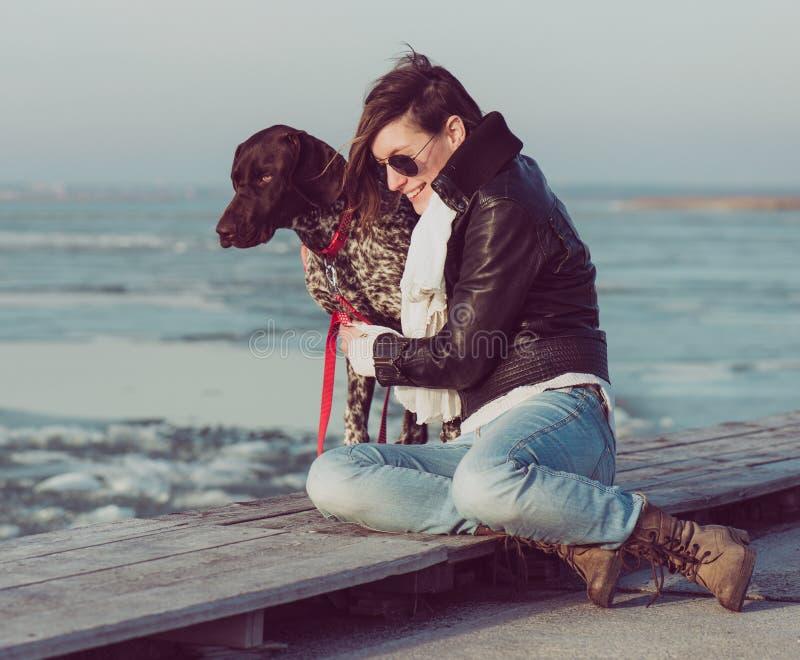Femme active de mode de vie avec la pose de chien extérieure photographie stock