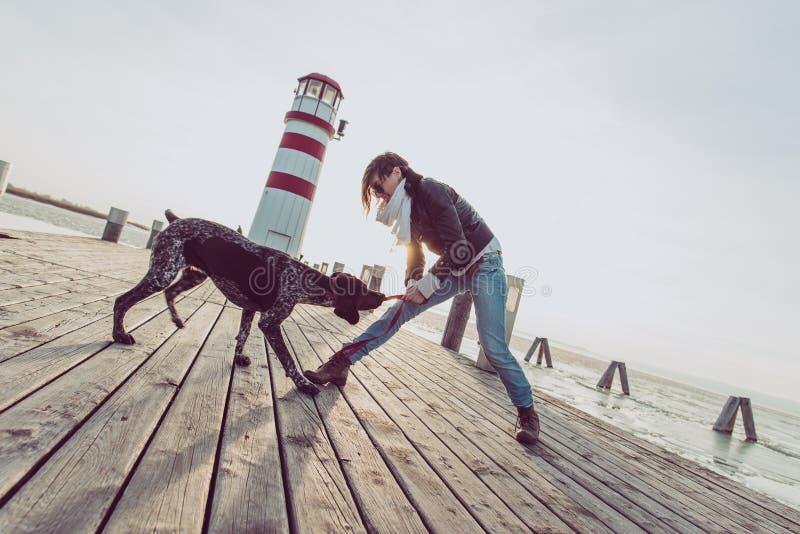 Femme active de mode de vie avec la pose de chien extérieure photos stock
