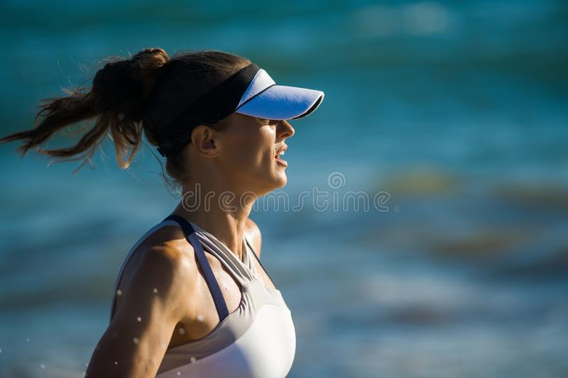 Femme active de sports dans des vêtements de sport fonctionnant contre la mer bleue photo stock