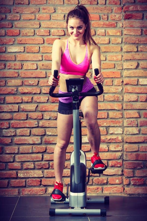 Femme active faisant faire du vélo de sport image stock