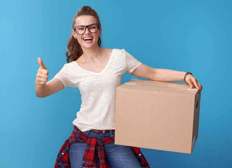 Femme active heureuse avec la boîte en carton montrant des pouces sur le bleu image stock