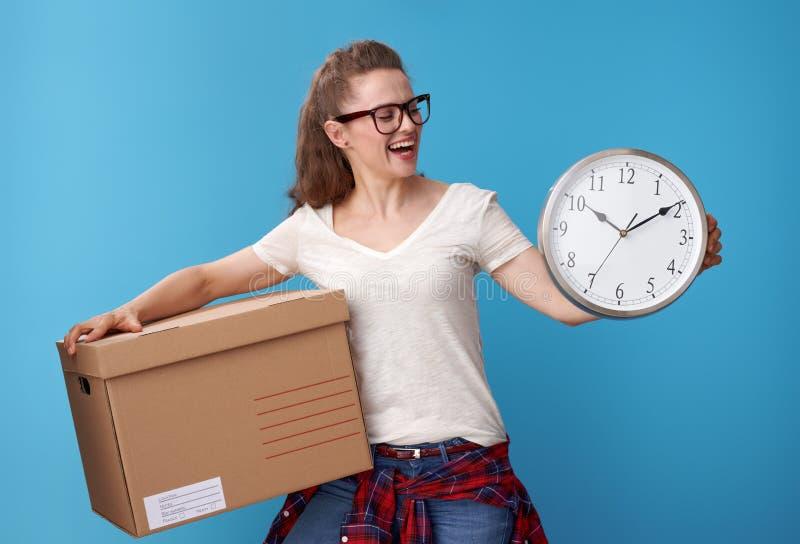 Femme active heureuse avec la boîte en carton regardant l'horloge sur le bleu images libres de droits