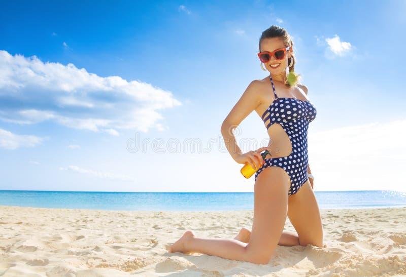 Femme active heureuse dans le tenue de plage sur la plage appliquant la lotion de bronzage photographie stock