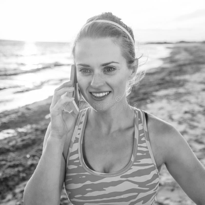 Femme active heureuse de forme physique sur le littoral parlant sur le smartphone photos libres de droits