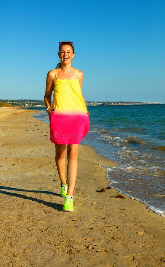 Femme active heureuse sur le littoral dans la marche de soirée images stock