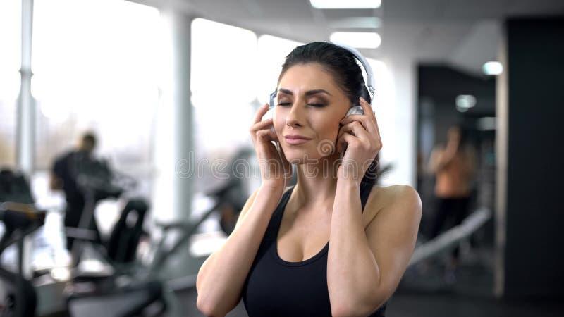 Femme active mettant sur des écouteurs et appréciant la musique dans le gymnase, inspiration de sport image stock