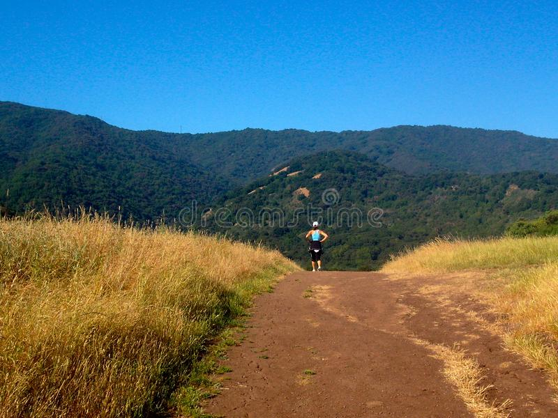 Femme active pulsant sur le chemin de montagne images libres de droits