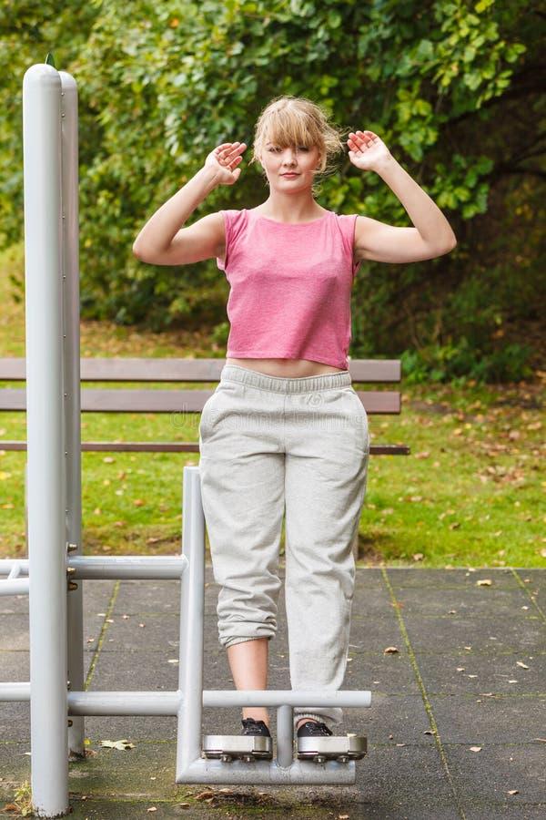 Femme active s'exerçant sur le backtrainer extérieur photos stock