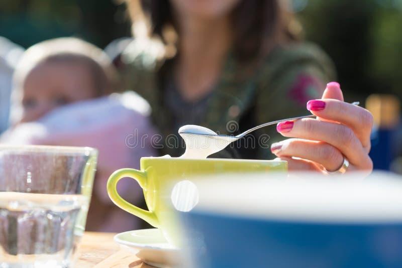 Femme administrant la mousse à la cuillère sur un cappuccino photos stock