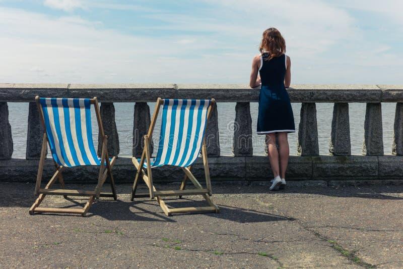 Femme admirant la mer de la promenade avec des chaises de plate-forme photographie stock libre de droits