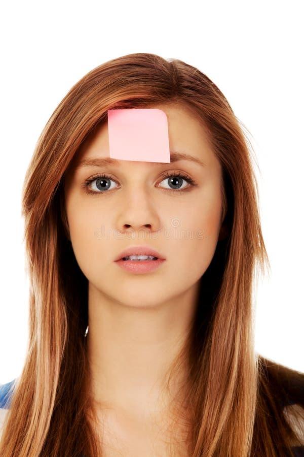 Femme adolescente avec les notes collantes sur le front images stock
