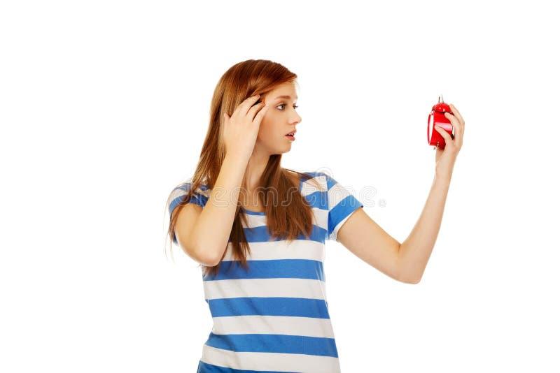 Femme adolescente choquée avec le réveil photos stock