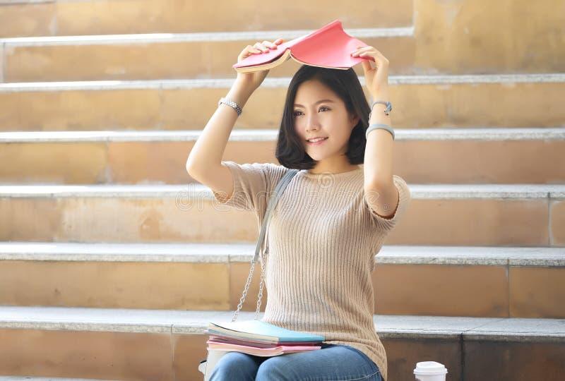 Femme adolescente d'étudiant avec des livres sur sa tête se reposant sur les escaliers de ville Les gens avec le concept d'éducat photo stock